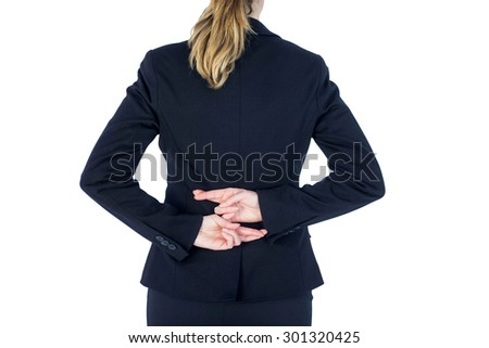 Close up pretty businesswoman with fingers crossed against a white wall - stock photo