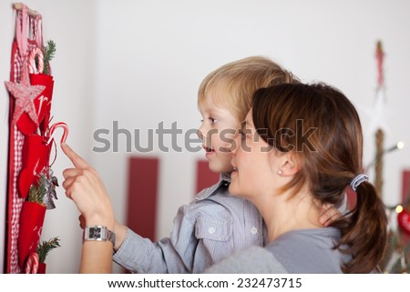 Close up Pretty Mom Carrying her Baby Boy While Introducing Christmas Decor Names that are Hanging on the Wall - stock photo
