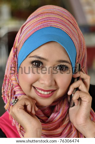 Close up Pretty Muslim Girl with hand phone - stock photo