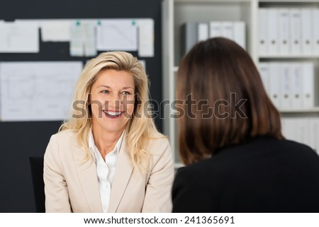Close up Pretty Smiling Adult Manager Woman Talking to her Subordinate at her Office. - stock photo
