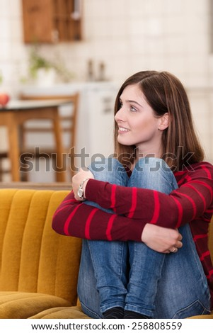 Close up Pretty Smiling White Woman Sitting on Couch and Hugging her Knees While Looking to her Upper Right Side. - stock photo