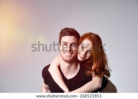 Close up Pretty Woman Hugging her Handsome Man from the Back While Looking at the Camera. Captured in Studio with Gray Background and Light Coming From the Left. - stock photo