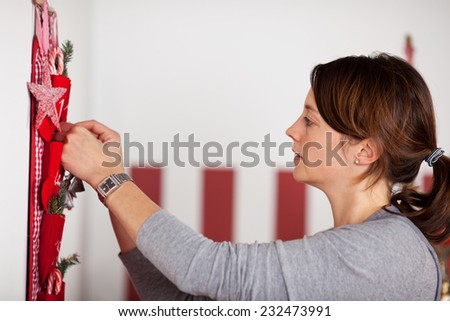 Close up Pretty Woman in Side View Fixing Red Christmas Decoration Hanging on the Wall Inside the House. - stock photo