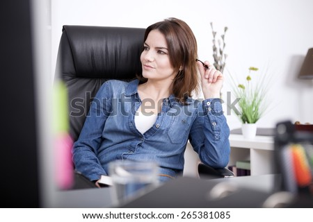 Close up Pretty Young Adult Businesswoman in Denim Outfit Sitting on her Chair at her Office While Looking to the Left of the Frame. - stock photo