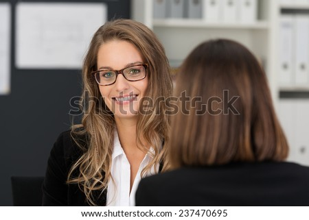 Close up Pretty Young Business Executive with Long Blond Hair and Eyeglasses Smiling at the Camera while Talking to her Female Co-worker at the Office. - stock photo