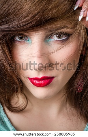 Close up Pretty Young Face of a Blond Woman with Blue and Green Eye Shadow and Red Lips Make up Looking at the Camera. - stock photo