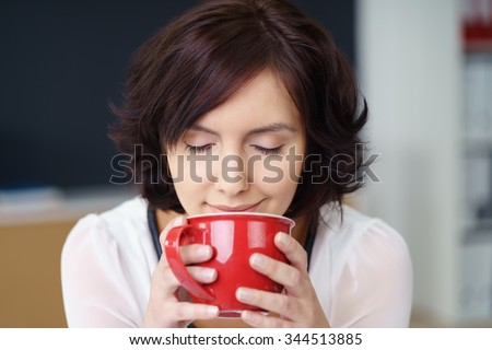 Close up Pretty Young Office Woman Smelling the Aroma of her Coffee Drink in a Red Cup with Eyes Closed. - stock photo