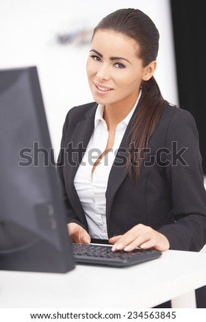 Close up Pretty Young Office Woman with Long Black Hair  Typing at the Keyboard on the Office Table and Take a Smile at the Camera for a While. - stock photo