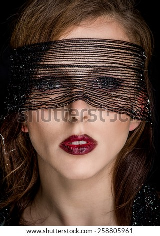 Close up Pretty Young Woman Face With Black Net Staring at the Camera on a Black Background. - stock photo