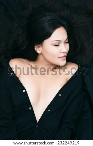 Close up Pretty Young Woman in Unbuttoned Black Blouse, Showing her Cleavage While Lying on Black Cloth Background. Captured in High Angle Shot. - stock photo