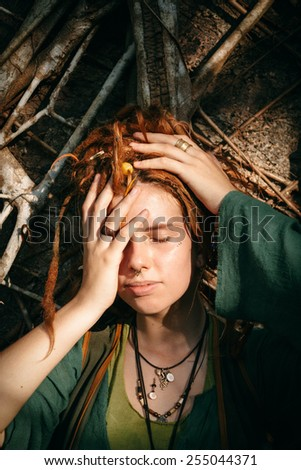 Close up Pretty Young Woman with Dreadlocks Blond Hair Covering her One Eye While Lying on Sticks. - stock photo
