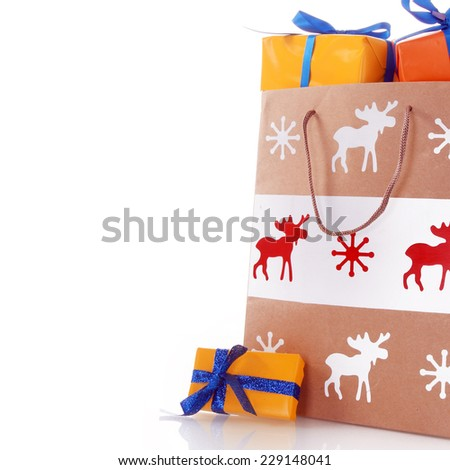 Close up Printed Christmas Paper Bag with Orange Presents Decorated with Blue Ribbons. Isolated on White Background. - stock photo