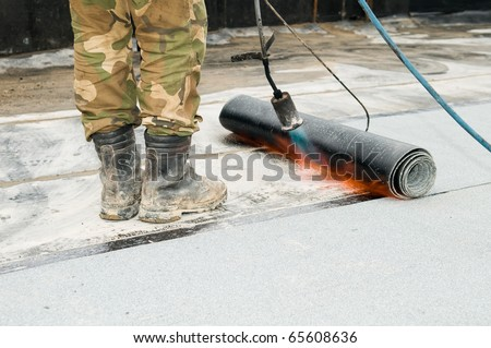 close-up process of roofing felt roll and torch blowpipes with open flame - stock photo