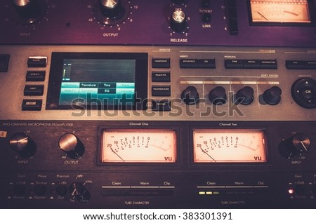 Close-up professional audio equipment with sliders and knobs at boutique recording studio.