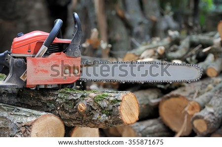 Close-up professional chainsaw blade cutting log of wood - stock photo
