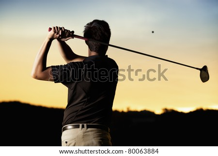 Close up professional golf player in black shirt teeing-off ball in twilight, view from behind. - stock photo
