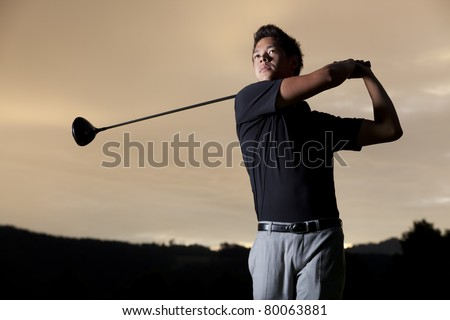Close up professional golf player in black shirt teeing-off with beautiful sunset in background, front view. - stock photo