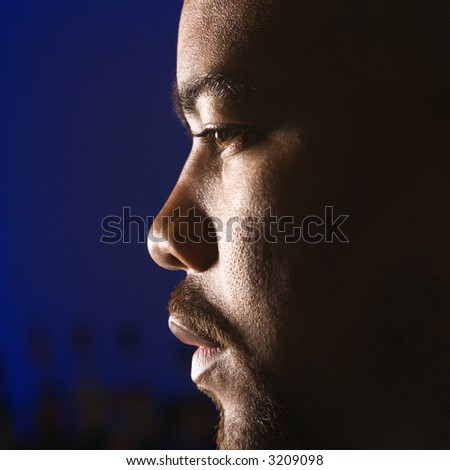 Close up profile of African American man in bar against glowing blue background.