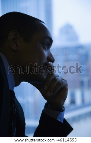 Close-up profile of an African-American mid-adult businessman with hand on chin in front of window. Vertical format. - stock photo