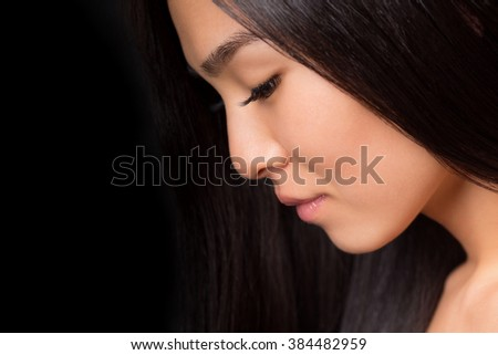 Close-up profile of asian lady looking down over black background. Beautiful lady with black bright hair in studio.