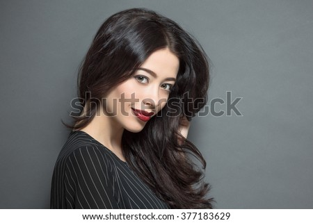 Close-up profile of fashion model woman with dark red lips happy smiling for photographer while posing for fashion magazine in studio. - stock photo