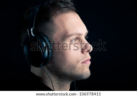 Close up profile of man with ear-phones on black background. - stock photo