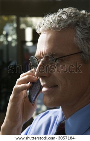 Close up profile of prime adult Caucasian man in suit talking on cellphone.