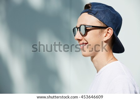 Close up profile of stylish smiling high school student boy wearing shades and snapback backwards posing against blank white wall background with copy space for your text or advertising content - stock photo