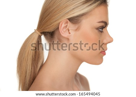 Close-up profile portrait of a beautiful blond woman with serious expression and looking down on a white background - stock photo