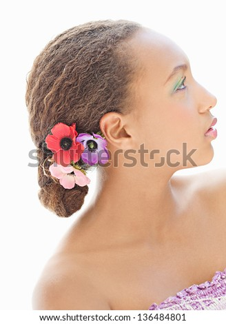 Close up profile portrait of a teenage girl wearing a make up and flowers on her hair, looking up ahead, being thoughtful. - stock photo
