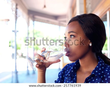 Close up profile portrait of a young business woman drinking water - stock photo