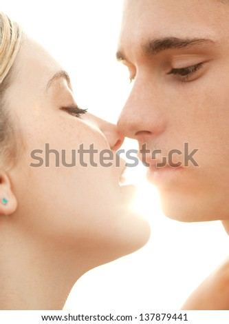 Close up profile portrait of a young couple in love, kissing against the sky, with the sun shining behind them and filtering through their mouths. - stock photo