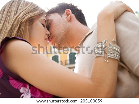Close up profile portrait of an attractive young couple being romantic and passionately kissing under the sun rays during a summer break vacation. First love and relationships lifestyle, outdoors. - stock photo