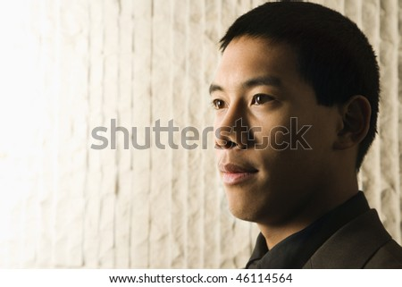 Close-up profile portrait of Asian young adult businessman. Horizontal format. - stock photo