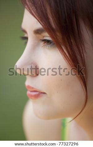 close-up profile portrait of sad young woman - stock photo
