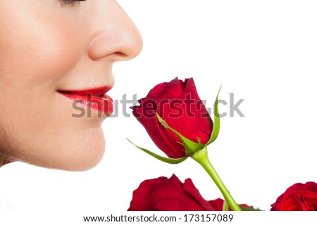 Close-up profile shot of a beautiful woman smelling a rose. Isolated on white. - stock photo
