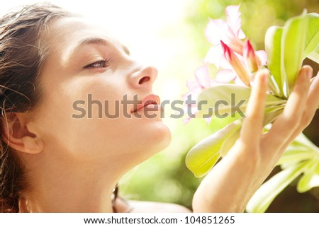 Close up profile view of a young attractive girl smelling a tropical pink flower in an exotic garden. - stock photo