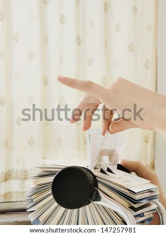 Close up profile view of a young business woman hand on her office desk carefully selecting a business card contact details from her roller deck database, interior. - stock photo