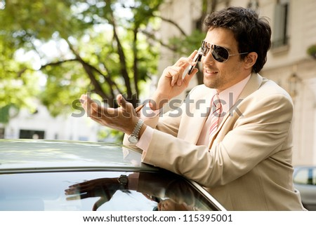Close up profile view of a young businessman having a conversation on his cell phone while leaning on his car on a tree aligned street. - stock photo
