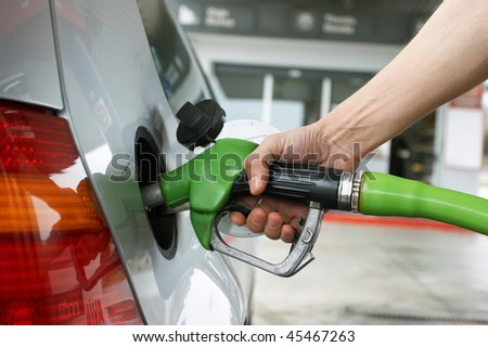 Close-up pumping gasoline on the car - stock photo