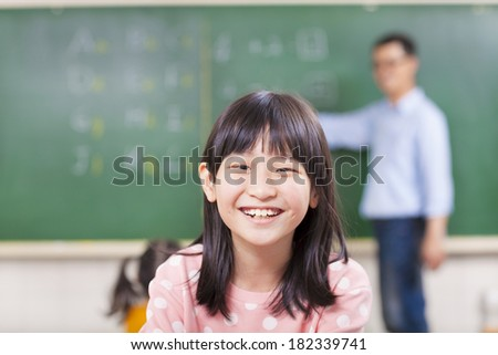 close-up pupils smiling in class with teacher - stock photo