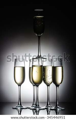 close-up pyramid of shiny champagne glasses with bubbles on grey background