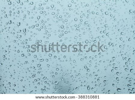 close up rain drops on wet windshield glass