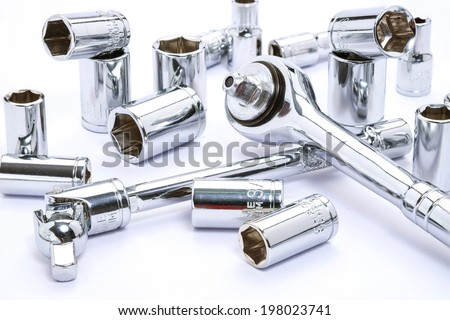 Close up Ratchet and a set of interchangeable heads for chrome socket wrench. Isolated on white background.