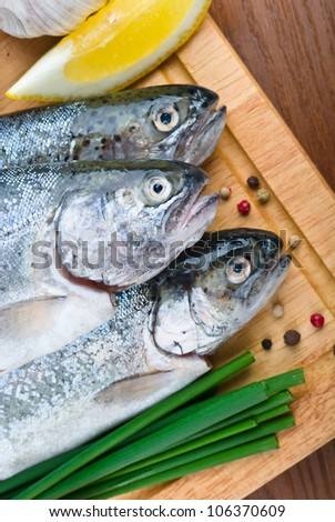 close-up raw fish trout with peppers, onions and lemon on a wooden background - stock photo