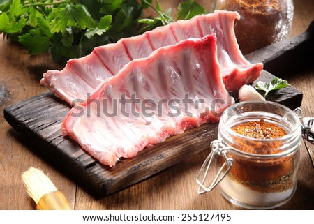 Close up Raw Pork Rib meat on Wooden Board with a Jar of Spicy Powder on the Side - stock photo