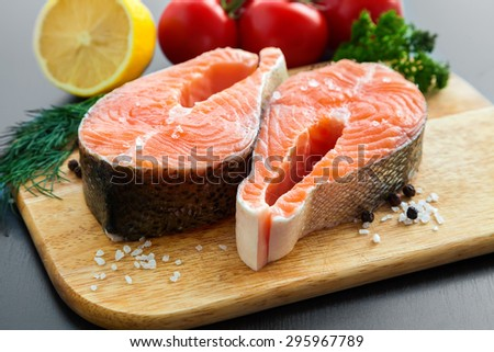 close-up raw salmon steaks with salt and pepper on a wooden board - stock photo