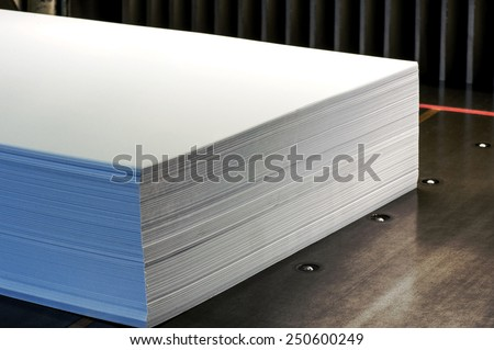 Close up Ream of Large Empty White Papers on a Wooden Platform Inside the Office. - stock photo