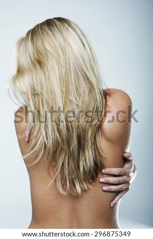 Close up Rear View of a Shirtless Blond Young Woman Hugging her Self While Looking on the Side Against Light Gray Wall Background. - stock photo