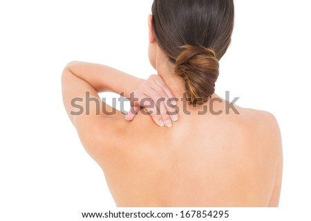 Close-up rear view of a topless young woman with shoulder pain over white background